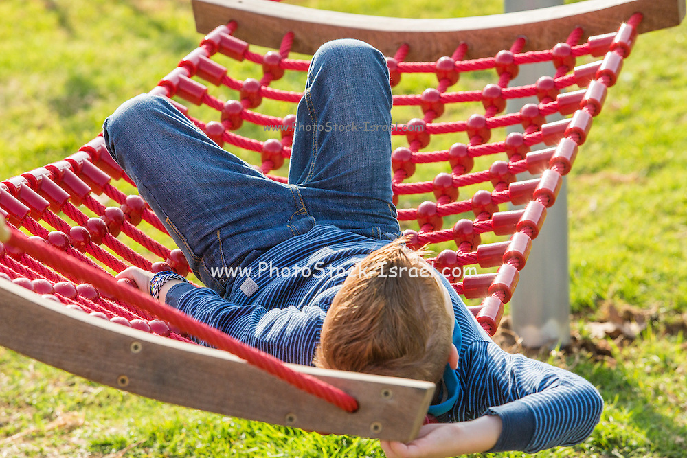 Red haired boy on a hammock in a garden