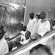 Burundian refugees' eyes gaze through the ambiance of the Phoenix Sky Harbor International Airport  while riding on an escalator while Arody Jimenez, on left, International Rescue Committee case worker guides them for baggage claim.