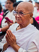 12 OCTOBER 2104 - BANG BUA THONG, NONTHABURI, THAILAND: A Buddhist nun prays for Apiwan Wiriyachai during the first day of his funeral rites at Wat Bang Phai in Bang Bua Thong, a Bangkok suburb, Sunday. Apiwan was a prominent Red Shirt leader, member of the Pheu Thai Party of former Prime Minister Yingluck Shinawatra, and a member of the Thai parliament. The military government that deposed the elected government in May, 2014, charged Apiwan with Lese Majeste for allegedly insulting the Thai Monarchy. Rather than face the charges, Apiwan fled Thailand to the Philippines. He died of a lung infection in the Philippines on Oct. 6. The military government gave his family permission to bring him back to Thailand for the funeral. He will be cremated later in October. The first day of the funeral rites Sunday drew tens of thousands of Red Shirts and their supporters, in the first Red Shirt gathering since the coup.    PHOTO BY JACK KURTZ