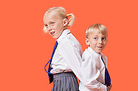 Happy young boy and girl in school uniform standing back to back over orange background