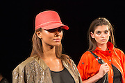 An orange cap, and an orange raincoat. By Monika Chiang at Spring 2013 Fashion Week in New York.