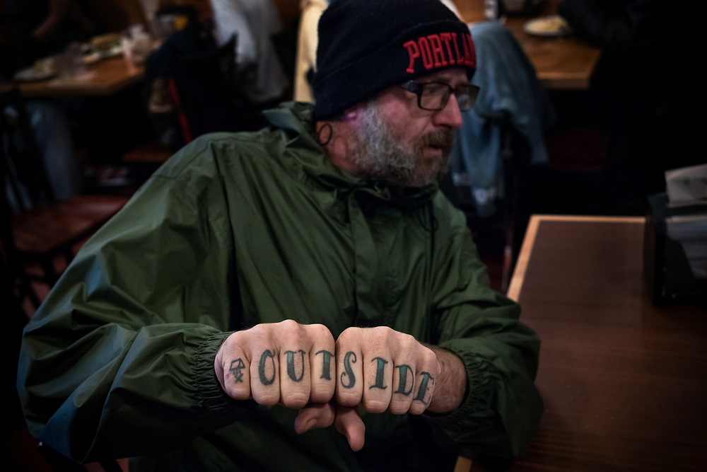 Jason, sitting for his reservation, shows off his ink, calling special attention to the tent and campfire tattooed on his left pinky.