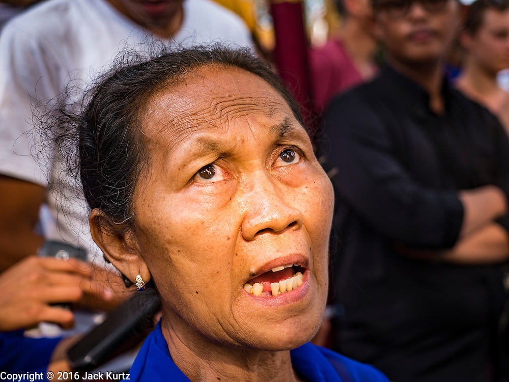 16 JULY 2016 - UBUD, BALI, INDONESIA: A woman chants a prayer while a sarcophagus burns during the mass cremation in Ubud. Local people in Ubud exhumed the remains of family members and burned their remains in a mass cremation ceremony Wednesday. Almost 100 people were cremated and laid to rest in the largest mass cremation in Bali in years this week. Most of the people on Bali are Hindus. Traditional cremations in Bali are very expensive, so communities usually hold one mass cremation approximately every five years. The cremation in Ubud concluded Saturday, with a large community ceremony.     PHOTO BY JACK KURTZ