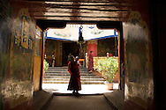 A young monk rings a bell at Tibetan Buddhist monastery in Shigatse, Tibet.