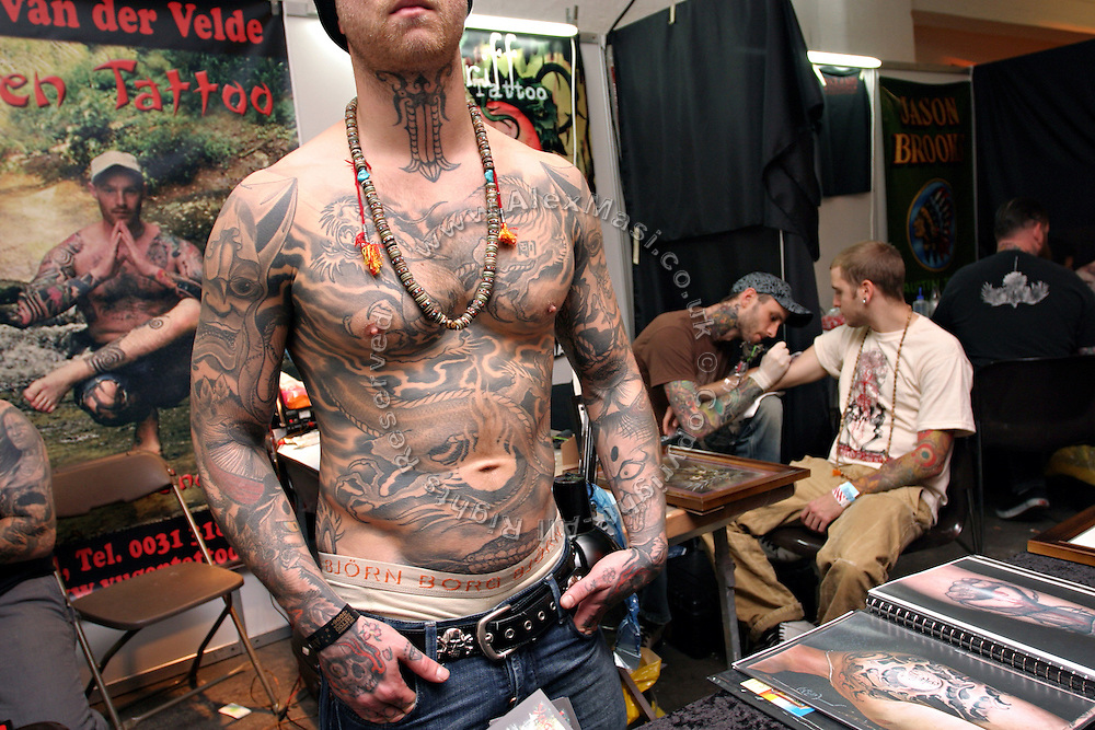 A man is exposing his tattoos while another man is being tattooed sitting on the nearby stall at the 2nd International Tattoo Convention in London on Saturday, Oct. 7, 2006, in London, UK. With over 15.000 visitors in three days during the 2005 edition, the event placed London in a central position in the tattoo world.  This year about 150 artists ,representing all the tattoo styles, are ticking away with their machines in a very exciting atmosphere. **ITALY OUT**....