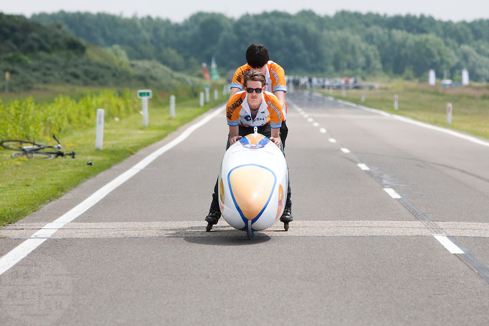 Jan Bos wordt begeleid tijdens de start. Het Human Powered Team Delft en Amsterdam presenteert de VeloX2, de fiets waarmee ze het wereldrecord willen verbreken dat nu op 133 km/h staat. Jan Bos, een van de rijders die het record gaat proberen te verbreken, gaat de strijd aan met zijn broer Theo Bos op de gewone racefiets. Jan wint uiteindelijk glansrijk en haalt 77,2 km/h.<br />