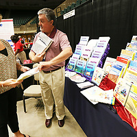 Kim Wyatt, an Inclusion teacher at Tupelo High School, talks with Kevin Gentry, a territory manager for Firelight Books out of Tyler Texas, about text book material for class during the The Mississippi Council for Exceptional Childen's statewide conference Tuesday afternoon at the BancorpSouth Arena in Tupelo.