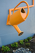 Artistic watering can rainwater downspout and swale.