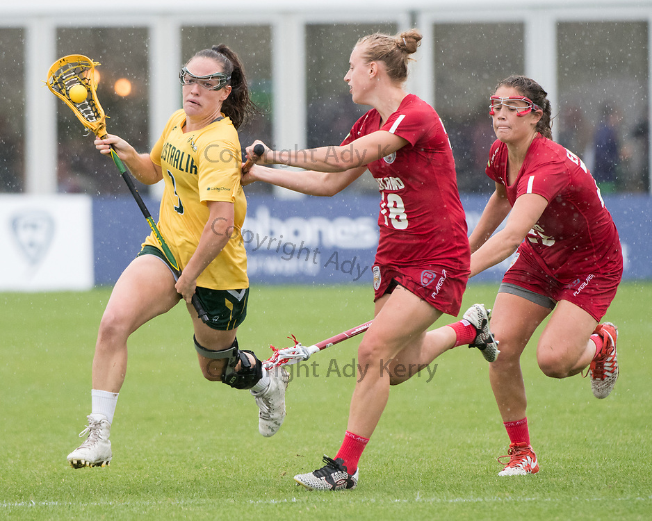 Australia's Rebecca Lane(3) is chased by Emma Oakley(18)ad Olivia Hompe at the 2017 FIL Rathbones Women's Lacrosse World Cup at Surrey Sports Park, Guilford, Surrey, UK, 15th July 2017