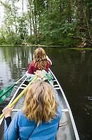 Two women paddling a canoe in the Washington State University Arboretum in Seattle, Washington, USA.