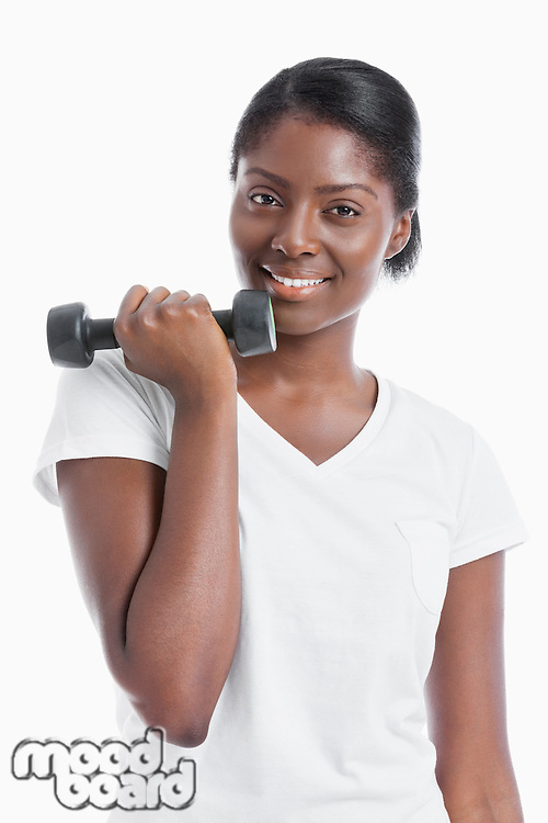 Portrait of an African American young woman with dumbbell over white background