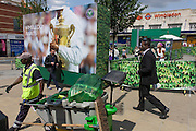 Day 2 of the annual lawn tennis championships women carry boxes and a council street sweeper empties bins near a large champions trophy billboard, outside the mainline and underground (subway) station in the south London suburb. The Wimbledon Championships, the oldest tennis tournament in the world, have been held at the nearby All England Club since 1877.