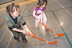 Children playing a game of indoor hockey in the sports hall of their local leisure centre,