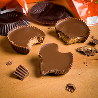 Peanut butter cup candy bitten into a heart shape to show love... or to show two in love with one in a love triangle... or to show multiple attempts.. keep on trying?