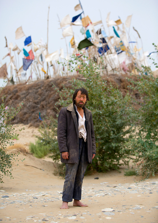 Uyghur Sufi man at Imam Asim Tomb in the Taklamakan desert, Xinjiang Uyghur Autonomous Region, China. This is a popular pilgrimage site, particularly during the month of May in the Taklamakan Desert.