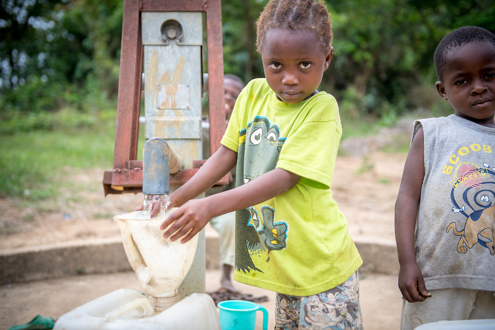 A young girl pumps water and a boy stands next to her watching in Ganta, Liberia