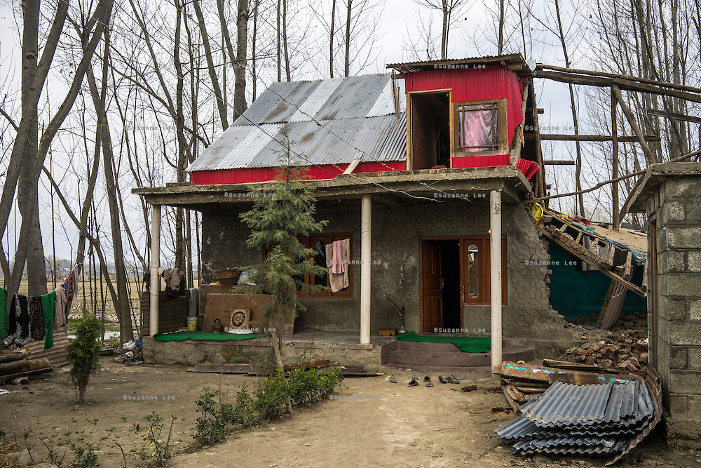 Abdul Ahad Ganai's house is seen here, destroyed by floods, in Narbal village, Jammu and Kashmir, India, on 24th March 2015. When the floods hit in the middle of the night, Abdul Ahad Ganai and his family with 5 children was lucky to escape with their lives despite half of his family home collapsing. Save the Children supported the family with emergency shelter kits, blankets, hygiene items, education kits and food baskets. Photo by Suzanne Lee for Save the Children