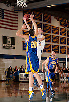 Gilford's Josh Joyce goes up for a shot over Franklin's Dana Bean during Tuesday night's varsity basketball action.  (Karen Bobotas/for the Laconia Daily Sun)
