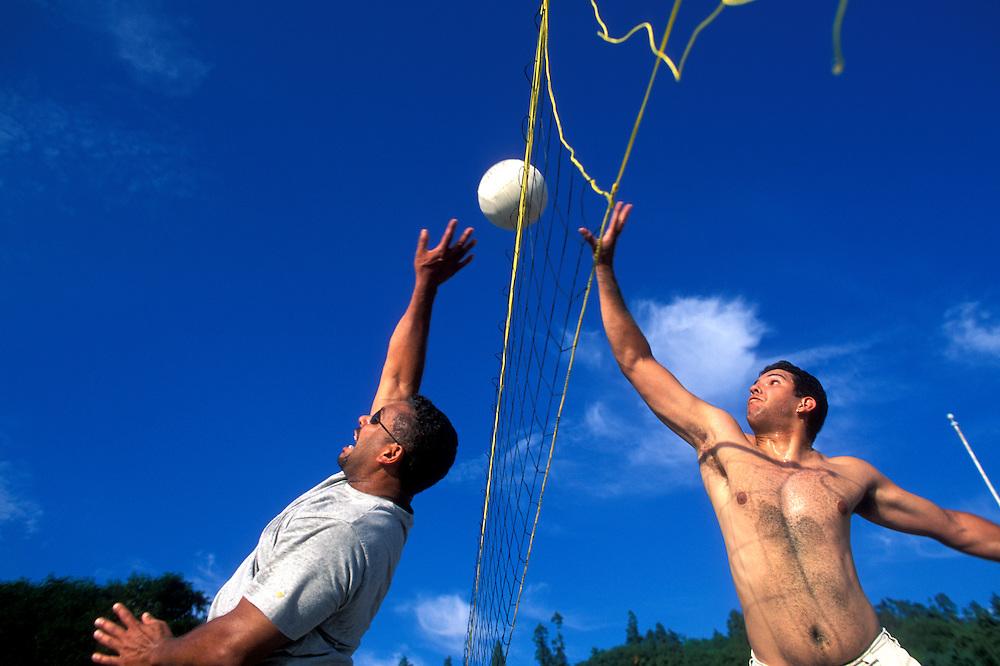 USA, Washington, Seattle, Friends play beach volleyball at Golden Gardens Park on summer afternoon