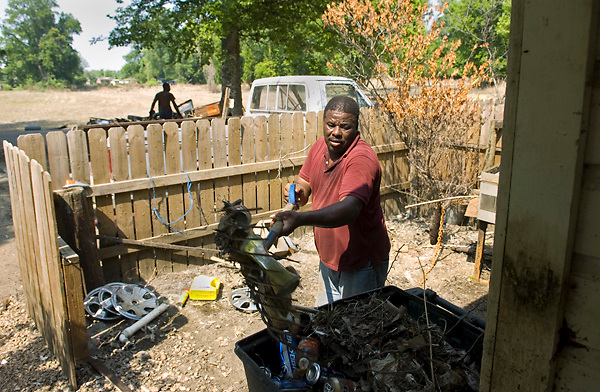 Jessie Rankin, foreground, and Carl Smith, background, help clean out the home of their friend Lee Arthur Carson on Hutson Street in the Kings Community of Vicksburg on Monday, June 13, 2011. The water level at the flood's crest was halfway up the front door. (Bryant Hawkins/The Vicksburg Post)