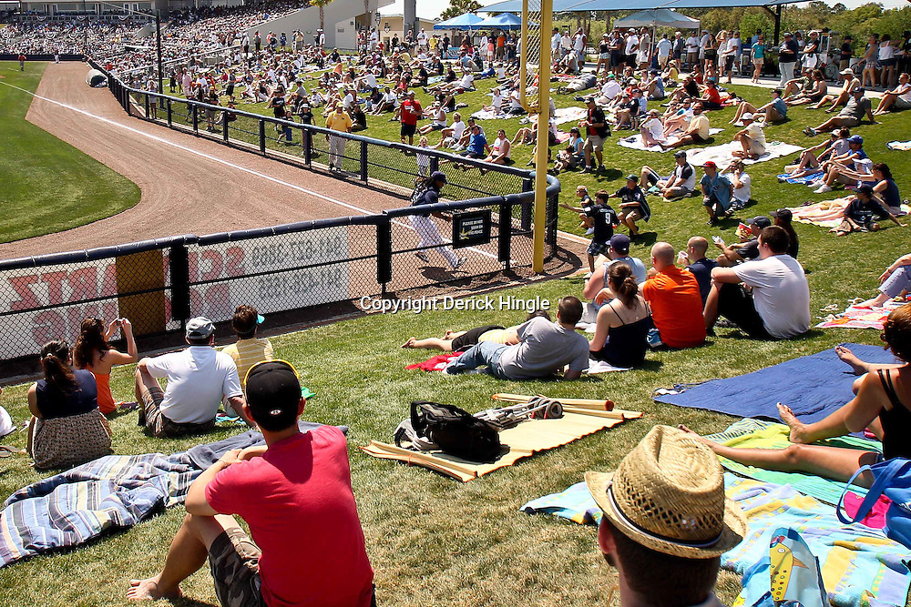 March 20, 2011; Port Charlotte, FL, USA; Tampa Bay Rays left fielder Manny Ramirez (24) chases down a ball hit down the left field line as fans watch from a grass levee during a spring training exhibition game against the Baltimore Orioles at Charlotte Sports Park.  Mandatory Credit: Derick E. Hingle-US PRESSWIRE
