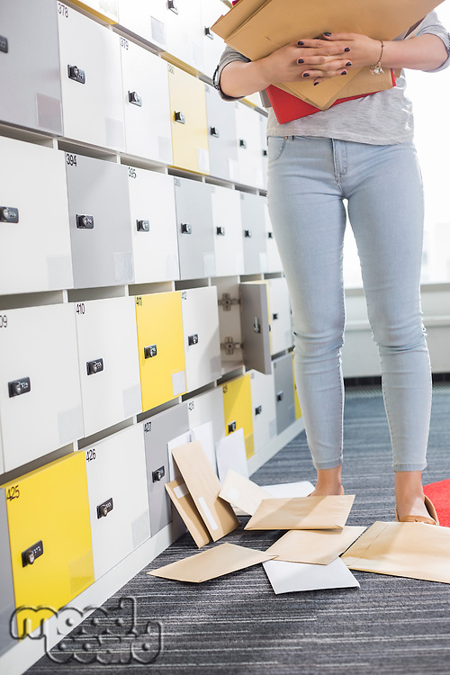 Low section of businesswoman standing by fallen documents in locker room at creative office