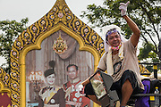 "03 DECEMBER 2013 - BANGKOK, THAILAND: An anti-government protestor waves from atop a truck in front of a portrait of Bhumibol Adulyadej, the King of Thailand, and his wife, Queen Sirikit in the Dusit district of Bangkok after police withdrew from their positions and allowed the protestors into the police security zone. Thousands of anti-government protestors entered the government offices in the Dusit district of Bangkok Tuesday after police stopped using tear gas and water cannons on the protestors. Protestors marched through the district waving Thai flags and chanting ""long live the King!"" Suthep Thaugsuban, leader of the protest movement, called it a partial victory but vowed to continue his battle to bring down the government of Yingluck Shinawatra.     PHOTO BY JACK KURTZ"
