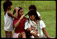 Kanamari women & kids pick lice from each other's hair in tribal village of Tres Unidos, Amazonas Brazil