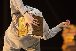 "© Licensed to London News Pictures. 24/01/2014. London, England. Pictured: Sidi Larbi Cherkaoui dances with the Koran. Belgian dancer/choreographer Sidi Larbi Cherkaoui's work ""Apocrifu"" uses the language of the body to explore apocryphal religious texts, accompanied by the polyphonic singing from the all-male Corsican vocal ensemble ""A Filetta"". Dancers: Sidi Larbi Cherkaoui, Dimitri Jourde and Yasuyuki Shuto. Performances at the Queen Elizabeth Hall, Southbank Centre from 24th to 25the January 2014. Photo credit: Bettina Strenske/LNP"