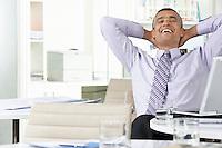 Businessman leaning back at office desk