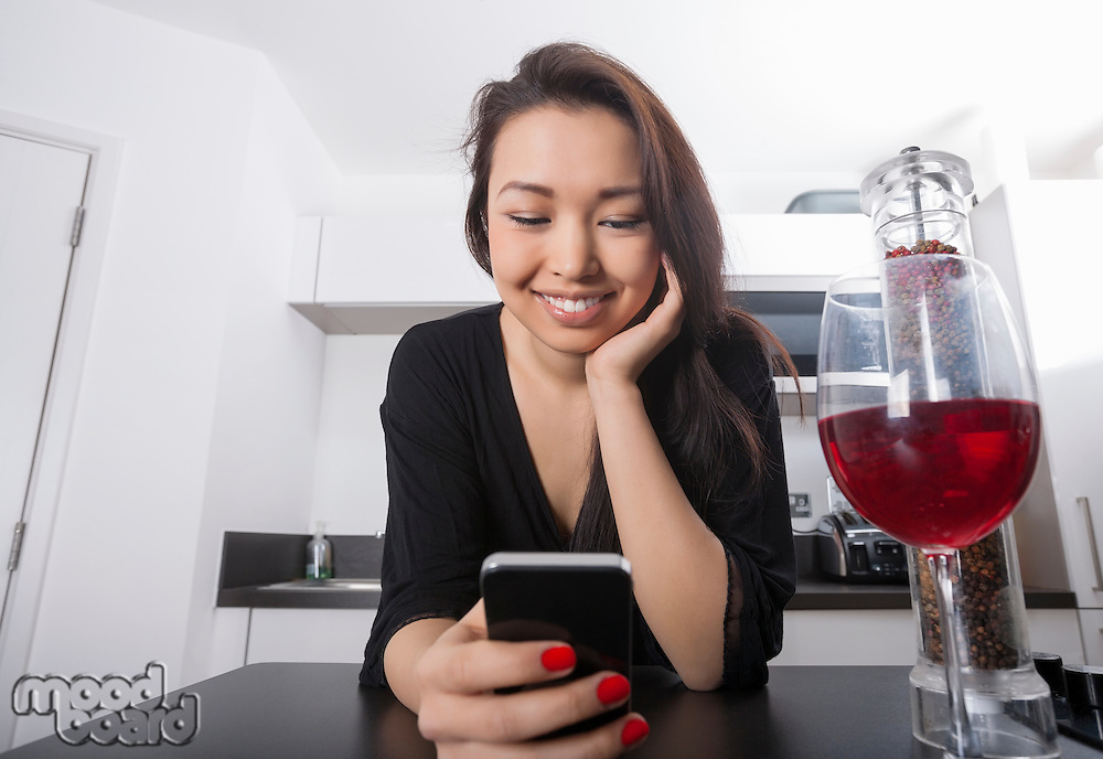 Beautiful young woman reading text message on smart phone at kitchen counter