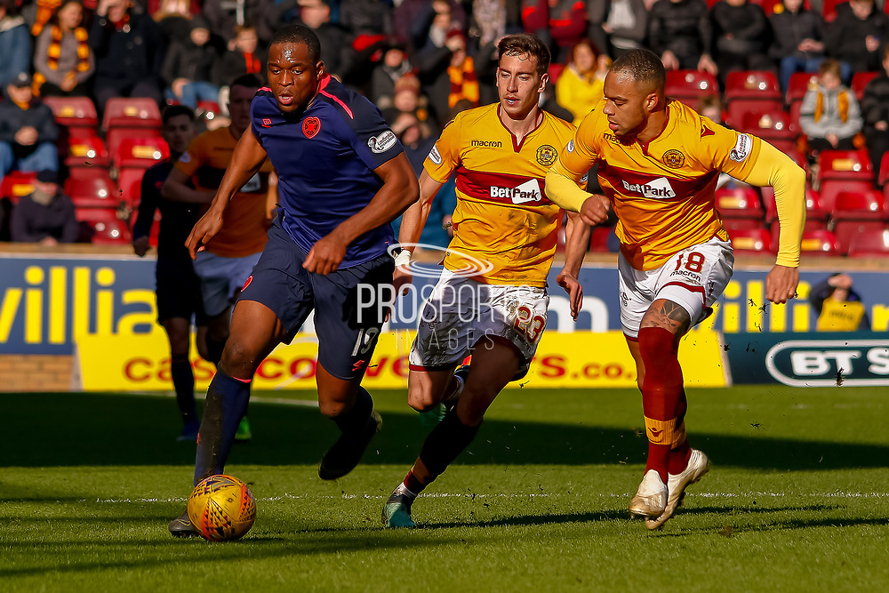 Uche Ikpeazu of Hearts has the beating of Charles Dunne of Motherwell and Alex Rodriguez Gorrin of Motherwell during the Ladbrokes Scottish Premiership match between Motherwell and Heart of Midlothian at Fir Park, Motherwell, Scotland on 17 February 2019.