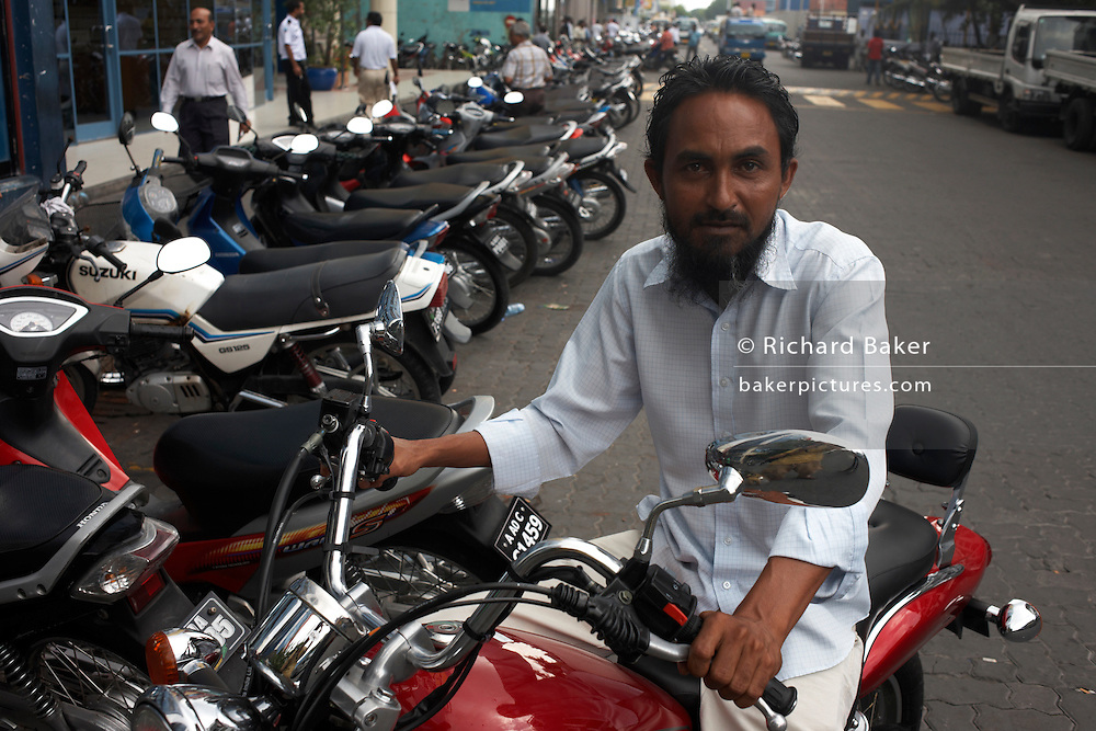 A helmetless Muslim rider looks for a parking space for his motorcycle in a crowded narrow urban street of Male, Maldives