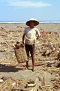 An old man rumages through driftwood on the beach near Prambanan, Java, Indonesia, which, if he finds suitable, hacks apart with his machete and stores in his woven basket.