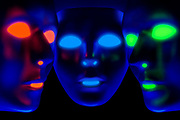 Three masks with glowing eyes, noses and mouths. Blacklight photography.