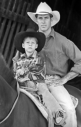 portrait of a cowboy and his cowboy son sitting on a horse