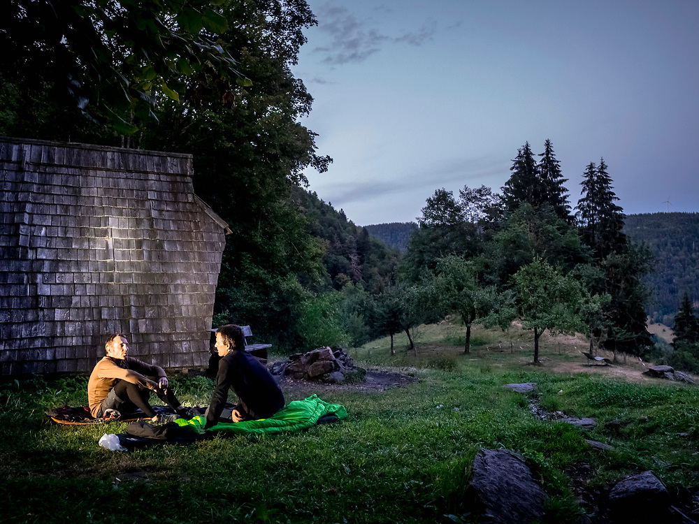 Two male hiker taking rest on meadow with sleeping bags, Baden-Wuerttemerg, Germany