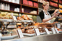 Fresh pastries displayed with young woman attendant in background