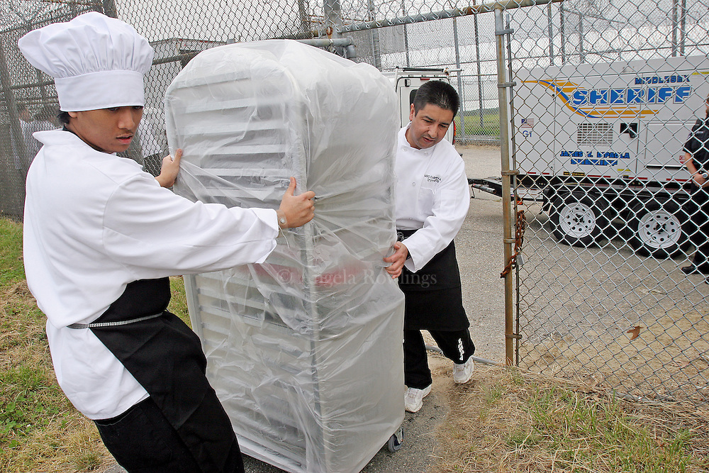 (060607  Billerica, MA)  Pheaktra Im, left, and Faber Aldana, graduates of the Inmate Culinary Arts Program at the Billerica House of Correction, cart out food for luncheon guests at the Billerica House of Correction, Wednesday,  June 6, 2007.    Staff photo by Angela Rowlings.