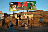 People walk under a campaign poster of President Hamid Karzai in Kabul, Afghanistan August 12, 2009. 41 candidates are due to run in Afghanistan's presidential elections which are to be held on August 20. The incumbent president Karzai is considered to be the frontrunner despite claims of corruption and what many consider an ineffectual government.