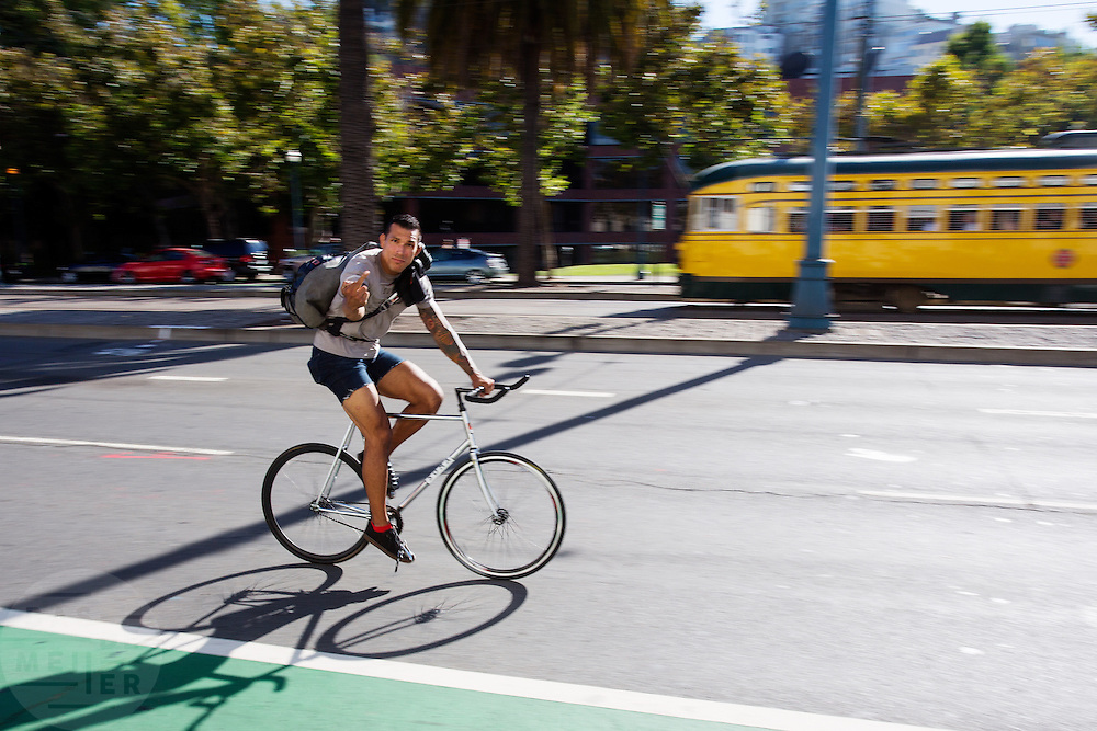 Een fietser in San Francisco steekt zijn middelvinger op naar de fotograaf. De Amerikaanse stad San Francisco aan de westkust is een van de grootste steden in Amerika en kenmerkt zich door de steile heuvels in de stad. Ondanks de heuvels wordt er steeds meer gefietst in de stad.<br /> <br /> A cyclist in San Francisco gives the photographer the finger. The US city of San Francisco on the west coast is one of the largest cities in America and is characterized by the steep hills in the city. Despite the hills more and more people cycle.