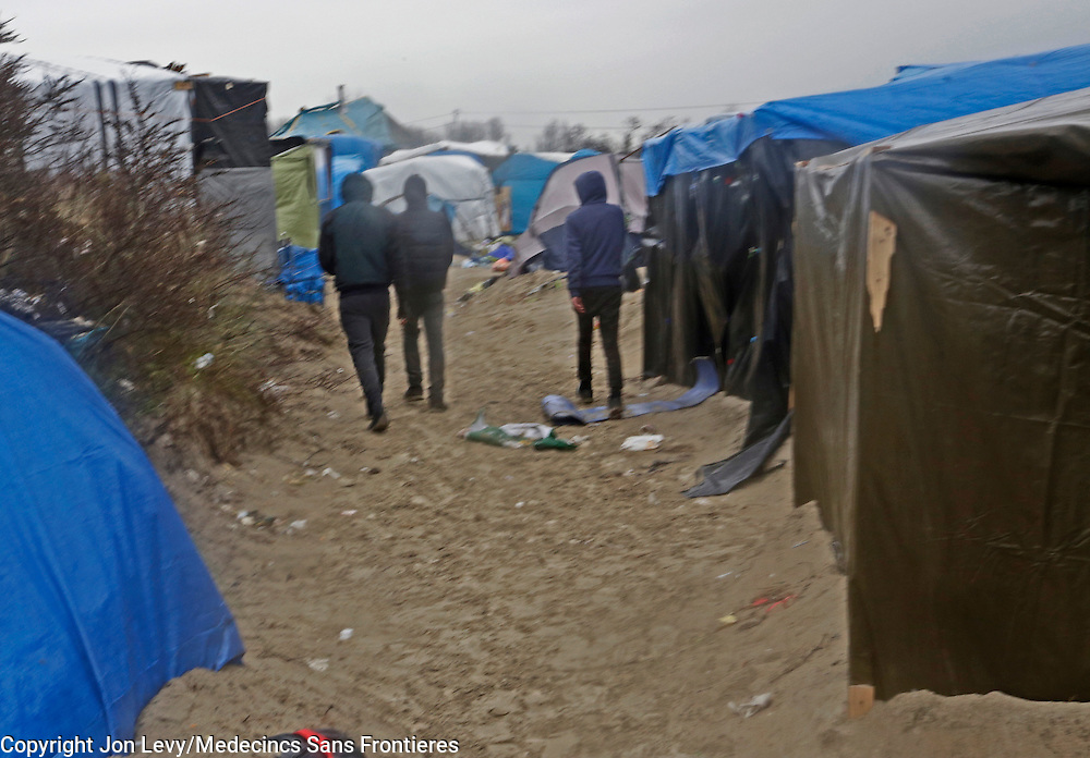 Three adolescent boys walks away after confronting writer AA Gill with a box cutter in an attempt to rob him in the Jungle refugee camp in Calais, northern France.<br />