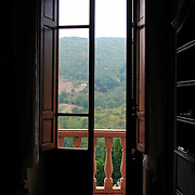 Hallway and open door to balcony with Tuscan hills beyond at Villa Rosa agriturisimo, Panzano in Chianti, Italy<br />