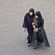 Two women walking in place Jemaa el-Fna in Marrakech, Morocco