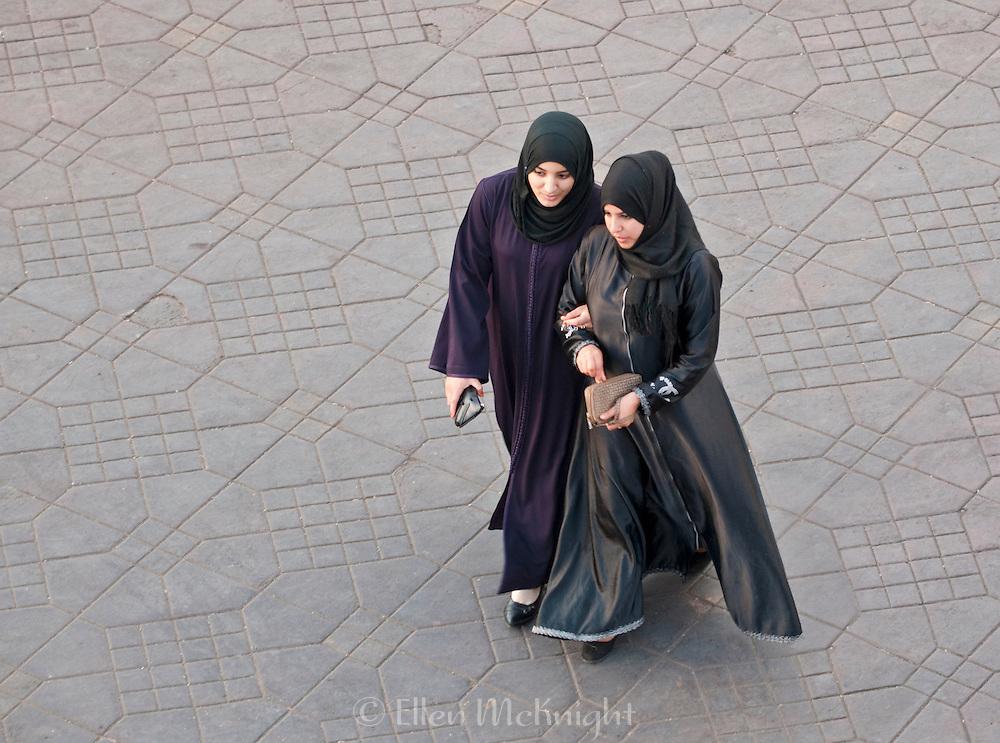Two women walking in place Jemaa el-Fna in Marrakech, Morocco