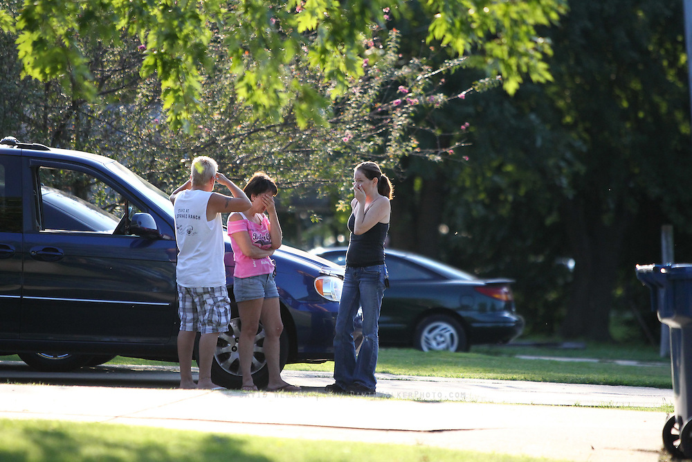 13 September 2010: Members of the subjects family stand a few houses down from the suspect's home. Around 5 p.m. on Monday, police received a call about a suicidal subject on West State Street in Springfield. A stand off ensued for the next four and half hours. Credit: David Welker/ Turfimages.com