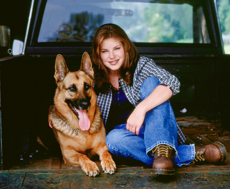 Young girl with red hair and braces sitting in the back of an old pickup truck with a German Shepherd dog.