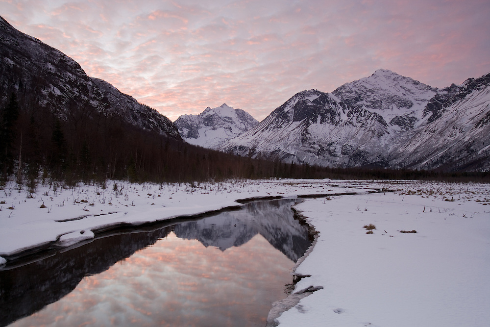 Winter alpenglow at sunrise on Eagle River valley and Polar Bear peak in Chugach State Park at Eagle River Nature Center in Southcentral Alaska. Winter. Morning.