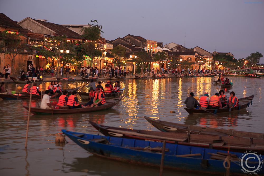 Local boats mix with tourist boats in the old town of Hoi An, Vietnam