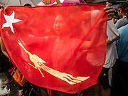 09 NOVEMBER 2015 - YANGON, MYANMAR: A woman holds up a NLD flag at NLD headquaters Monday. Thousands of National League for Democracy (NLD) supporters gathered at NLD headquarters on Shwegondaing Road in central Yangon to celebrate their apparent landslide victory in Myanmar's national elections that took place Sunday. The announcement of official results was delayed repeatedly Monday, but early reports are that the NLD did very well against the incumbent USDP.     PHOTO BY JACK KURTZ